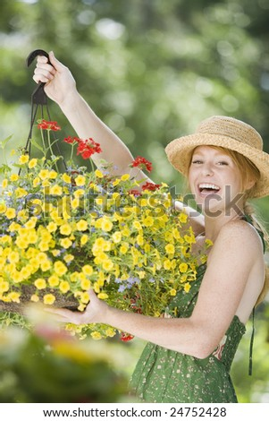 Young woman holding a hanging flower basket and smiling - stock photo