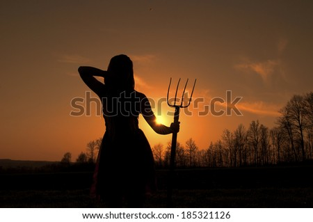 Young woman holding a hay fork at sunset - stock photo