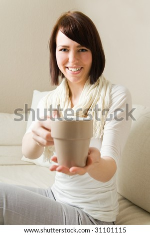 Young woman holding a hot cup of tea - stock photo