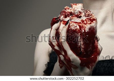 Young woman holding a human heart  - stock photo