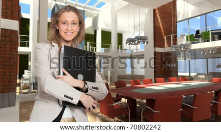 Young woman holding a laptop in the boardroom of a modern office - stock photo