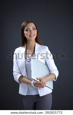 Young woman holding a laptop, standing on gray background - stock photo