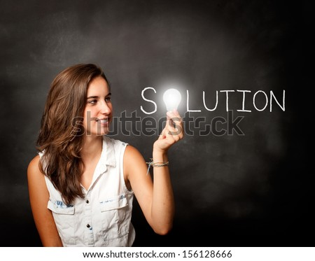 young woman holding a lightbulb composing solution word - stock photo