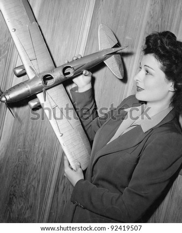 Young woman holding a model plane - stock photo