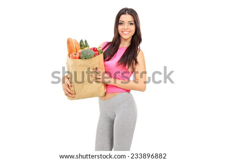 Young woman holding a paper bag full of groceries isolated on white background - stock photo