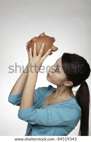 young woman holding a piggy bank hoping she has some money inside - stock photo
