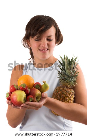 Young woman holding a pile of various fruits in her hands and pulling a face as if she doesn't really like it - stock photo