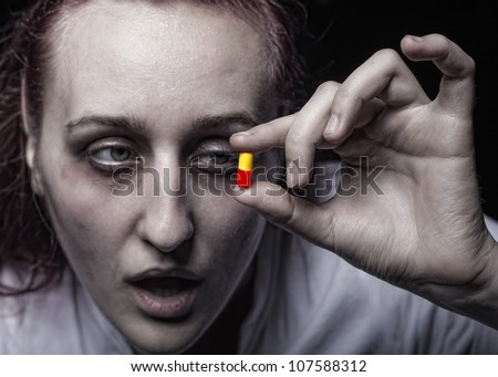 Young woman holding a pill addict. Focus on hands