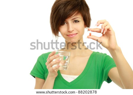 Young woman holding a pill and water, isolated on white background - stock photo