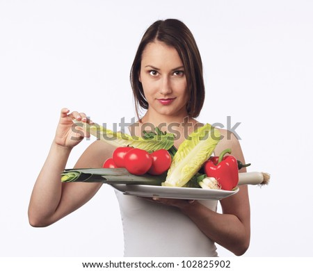 Young woman holding a plate with fresh vegetables