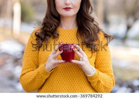 Young woman holding a red apple - stock photo