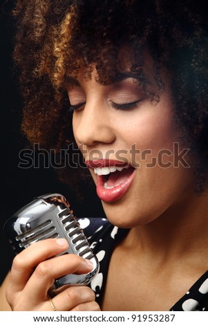 young woman holding a retro microphione and singing - stock photo