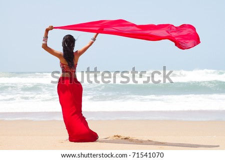 young woman holding a sarong on windy beach - stock photo