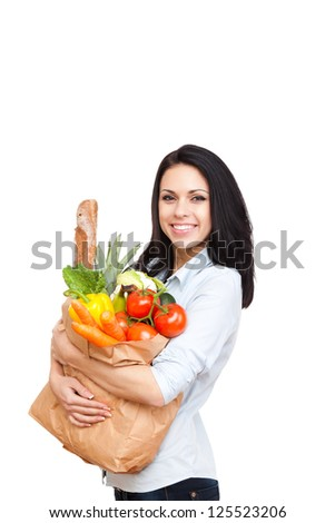 young woman holding a shopping bag full of vegetables groceries, happy female isolated on white background