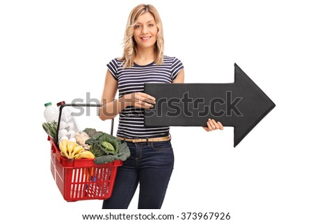 Young woman holding a shopping basket and a big black arrow pointing right isolated on white background