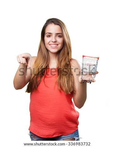 young woman holding a shopping cart pointing to front - stock photo