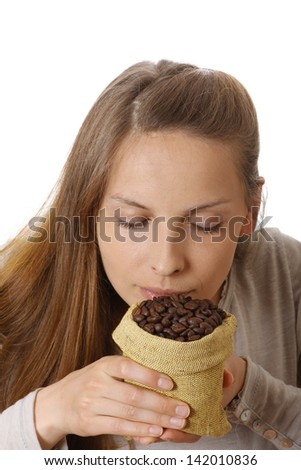 young woman holding a small bag of coffee beans
