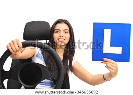 Young woman holding a steering wheel and an L-sign seated on a car seat isolated on white background - stock photo
