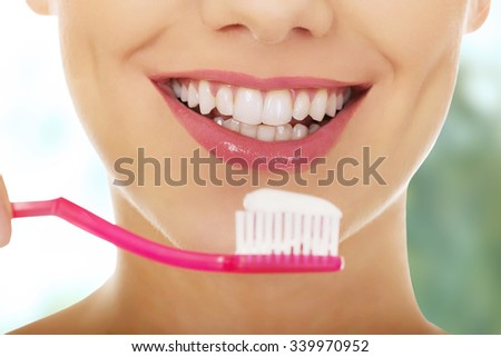 Young woman holding a toothbrush. - stock photo
