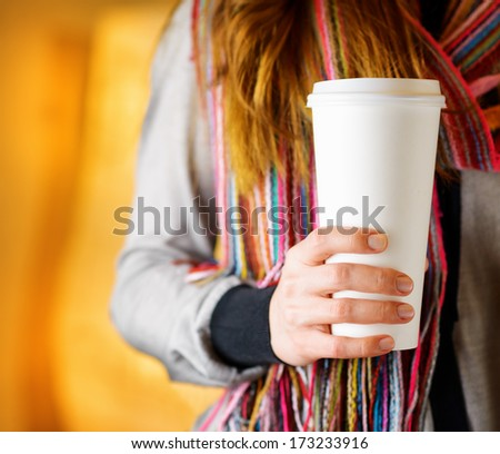 Young woman holding a tumbler of coffee in cafe. - stock photo