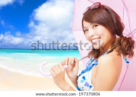 young woman holding a umbrella with beach background - stock photo