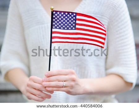 Young woman holding american flag. Independence Day concept.