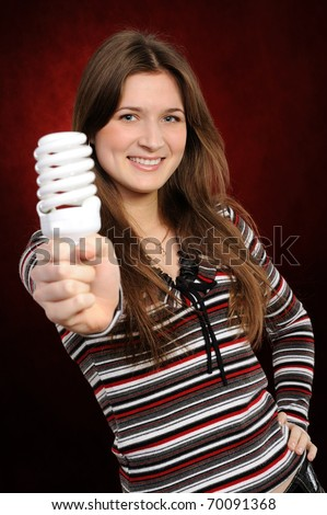 Young woman holding an fluorescent light bulb. On a red background