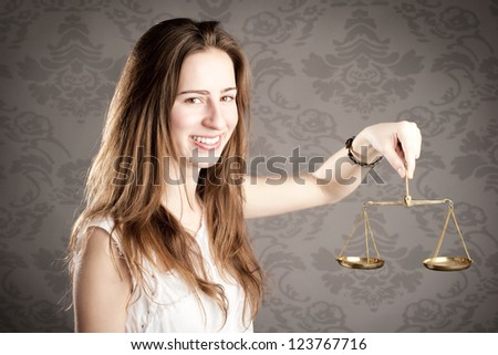 young woman holding an hourglass looking at camera - stock photo