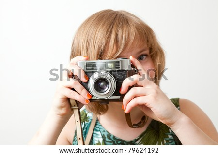 Young woman holding an old vintage camera - stock photo