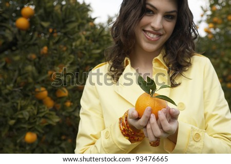 Young woman holding an orange while standing in an orange grove. - stock photo