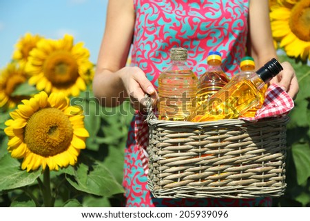 Young woman holding basket with bottles of oil in field - stock photo