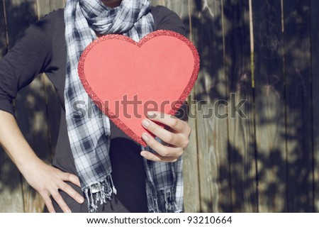 Young woman holding big red heart in her hand, copy space - stock photo