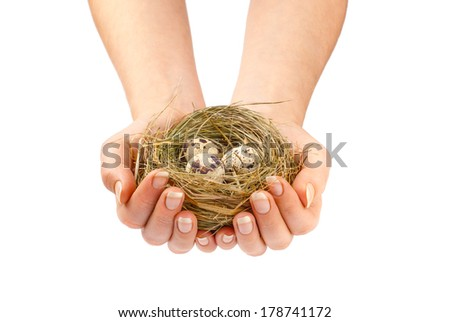 Young woman holding birds nest over white background