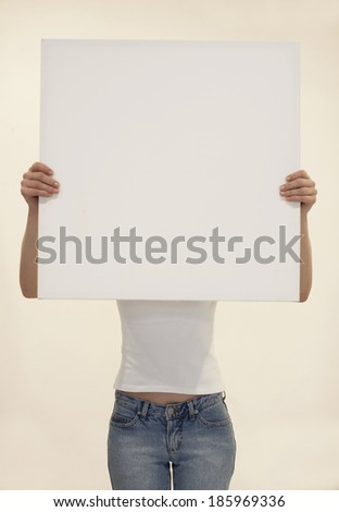 Young woman holding blank piece of paper - stock photo