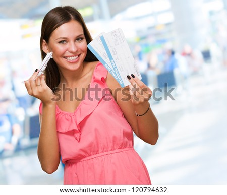 Young Woman Holding Boarding Pass And Miniature Airplane at the airport - stock photo