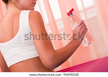 Young woman holding bottle of water - stock photo