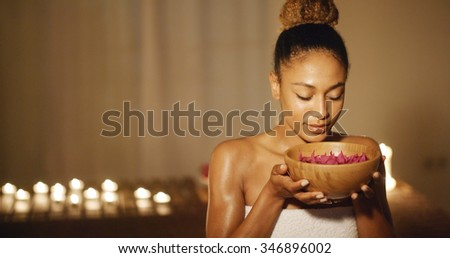 Young woman holding bowl with aromatic water and petals for spa
