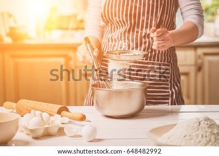 Young woman holding bowl with dough and whisk, closeup
