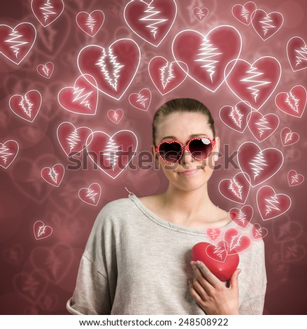 young woman holding broken heart - stock photo