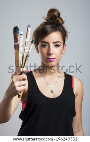 Young woman holding brush on gray background - stock photo