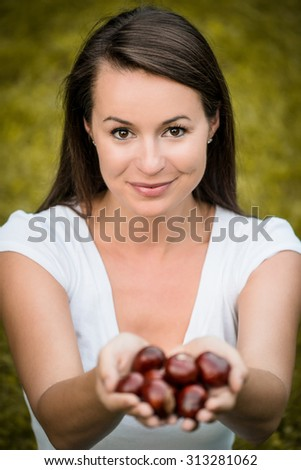 Young woman holding chestnuts in open hands outdoor - stock photo