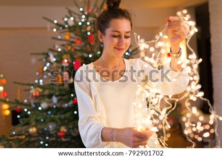 Young woman holding Christmas lights