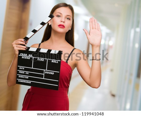 Young Woman Holding Clapper Board in a passage way