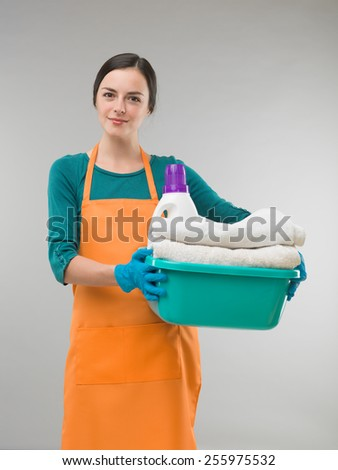 young woman holding clean towels and detergent in basin against grey background. studio photography - stock photo