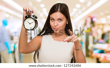 Young Woman Holding Clock And Pointing at a mall - stock photo
