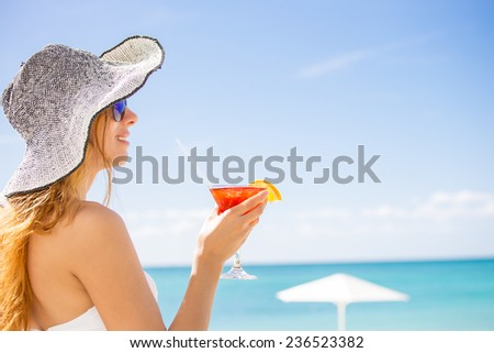 Young woman holding cocktail glass on the beach enjoying sunny weather looking on the ocean view. Tropical paradise getaway travel vacation tourism concept. Positive emotion face expression  - stock photo