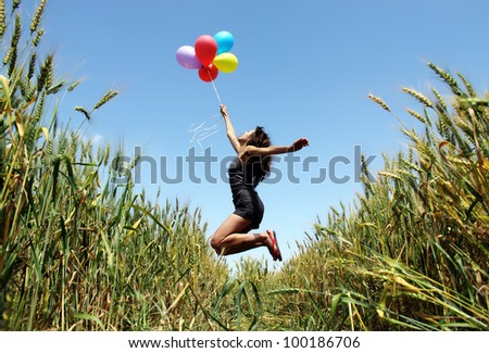 Young woman holding colorful balloons and flying over a meadow - stock photo
