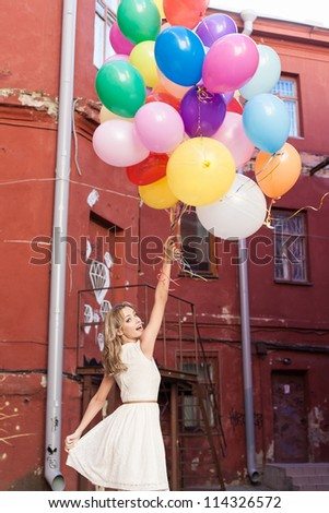 Young woman holding colorful latex balloons, urban scene, outdoors - stock photo