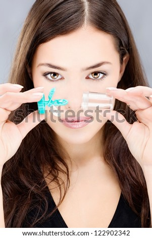 Young woman holding contact lenses wash container in front of her face