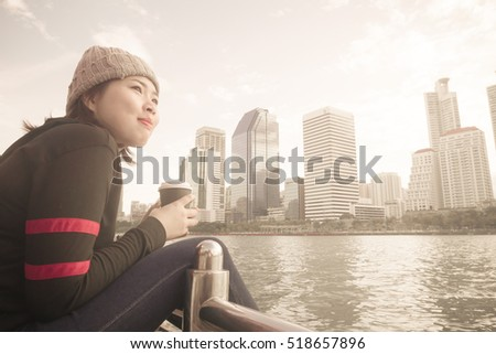 Young woman holding cup of coffee and sitting in the center public park